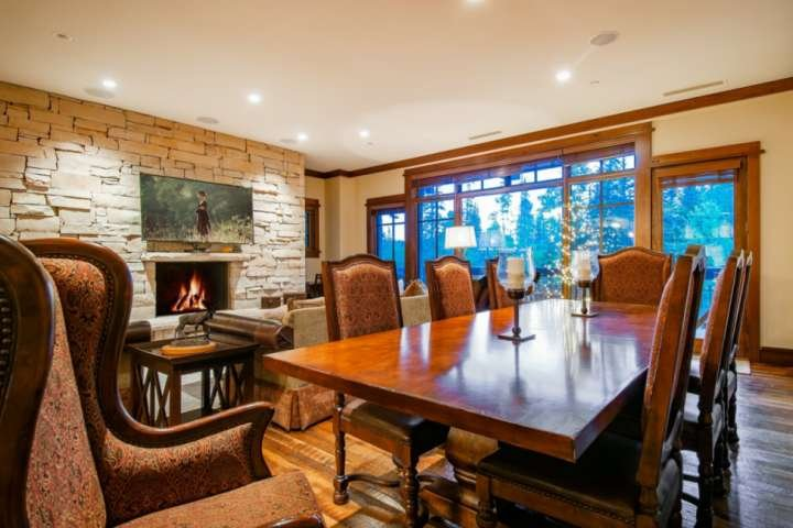 Formal dining area with mahogany dining table for 8, stone fireplace with large picture window