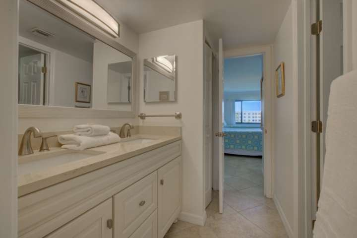 Jack and Jill bathroom with dual sinks, solid stone counters, tile floors and a bathtub/shower combo.  The water closet is enclosed with a pocket door