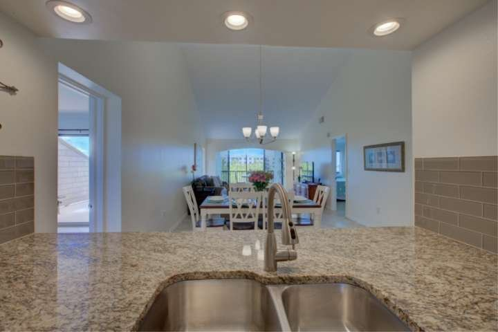 Solid stone counters and fully stocked kitchen is open to main living space and dining area.