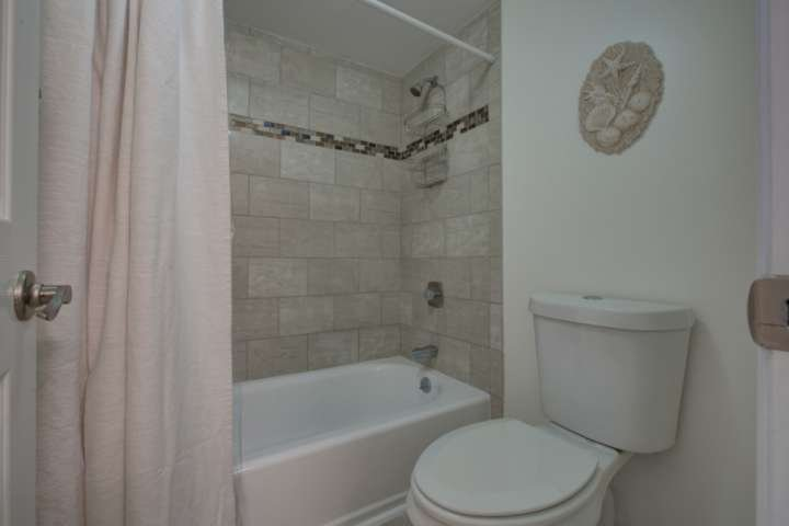 This jack and jill bathroom has a shower/tub combo with a sliding pocket door for privacy.