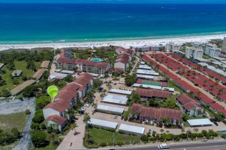 Aerial view of Siesta Dunes complex with private beach, large communal swimming pool and tennis courts.