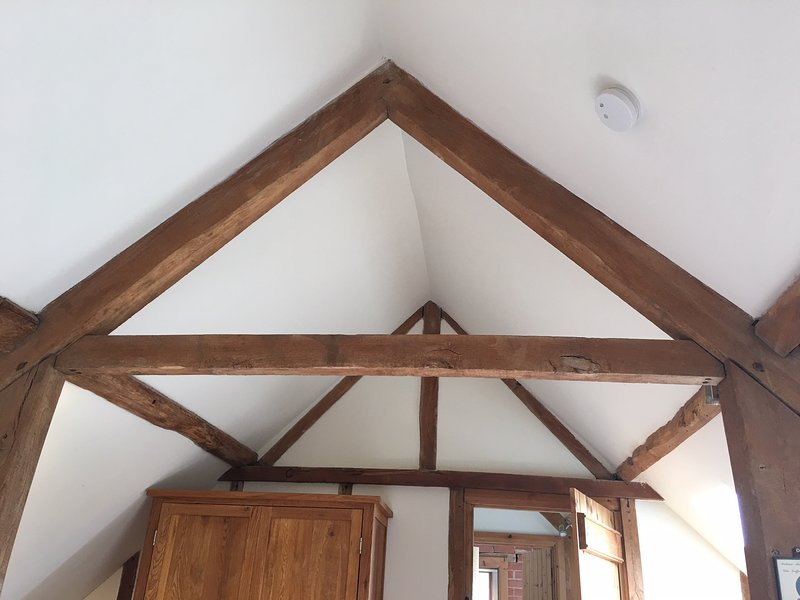 Exposed beams reaching into the vaulted ceiling in the upstairs of the Barn