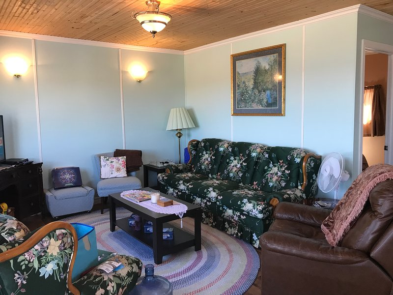 Sala de estar con un montón de sillas para sentarse y relajarse.