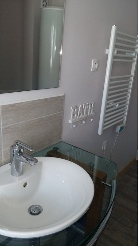Bathroom with bath, basin, toilet and hot water tank.