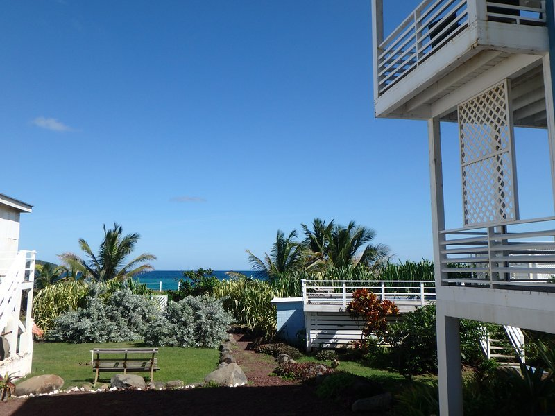 view from driveway and parking area past shared salt-water pool, towards beachfront gardens