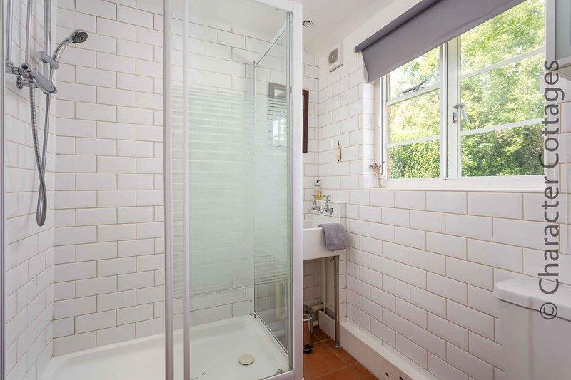 El cuarto de baño tiene una ducha a ras de, lavabo y WC