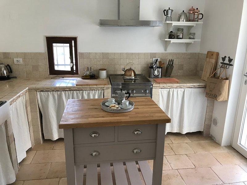 Kitchen with artisan butchers block stone flooring plus door to external covered veranda.