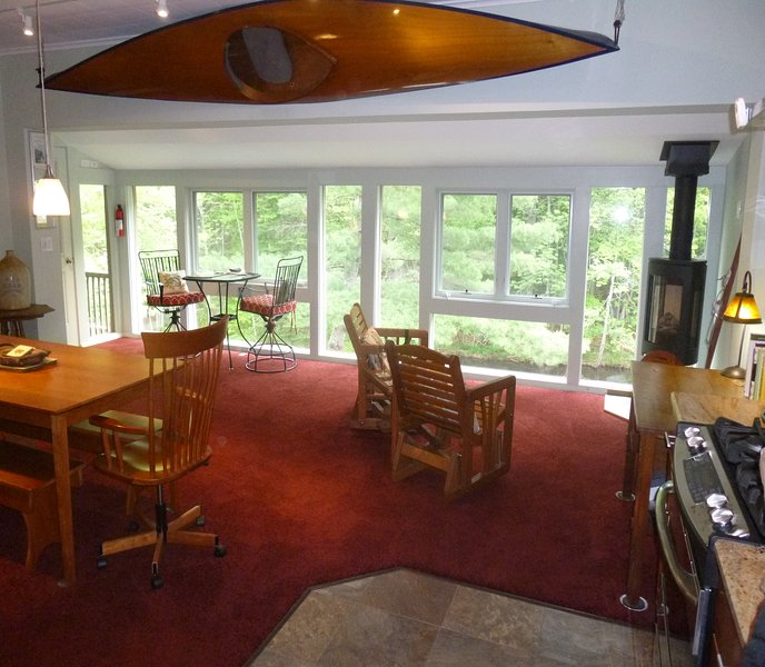 Poolside great room with floor-to-ceiling windows, plush carpets, cherry furniture, Jotul gas stove.