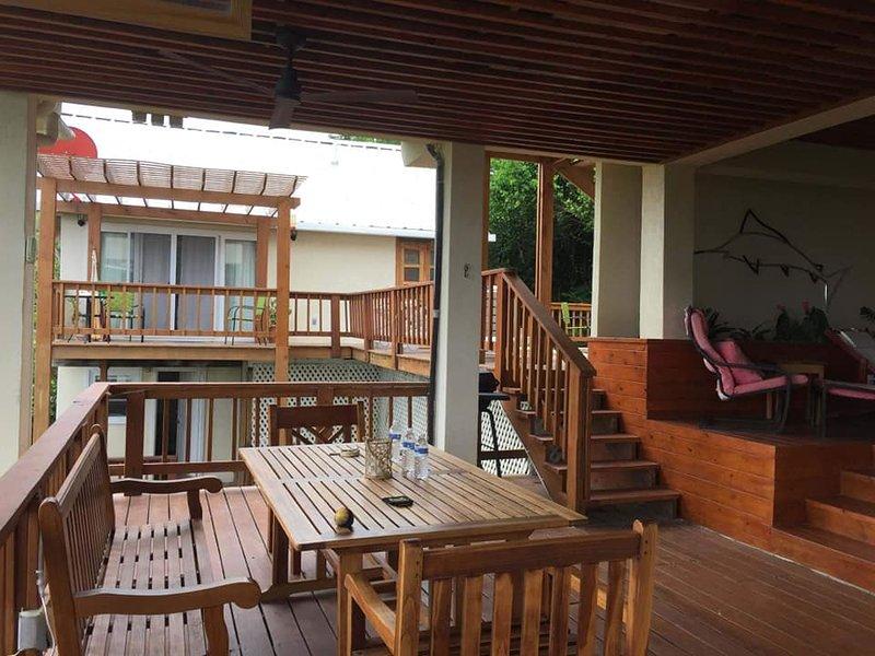 Más cubierta espacio al aire libre con mesa de comedor, ventilador de techo, parrilla y hamaca en esta área