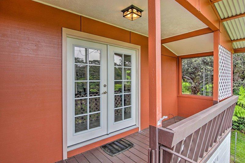Mira hacia el entorno exuberante selva tropical desde el porche.