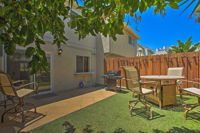 The condo features a private backyard, pool access, and sleeps 8 travelers.