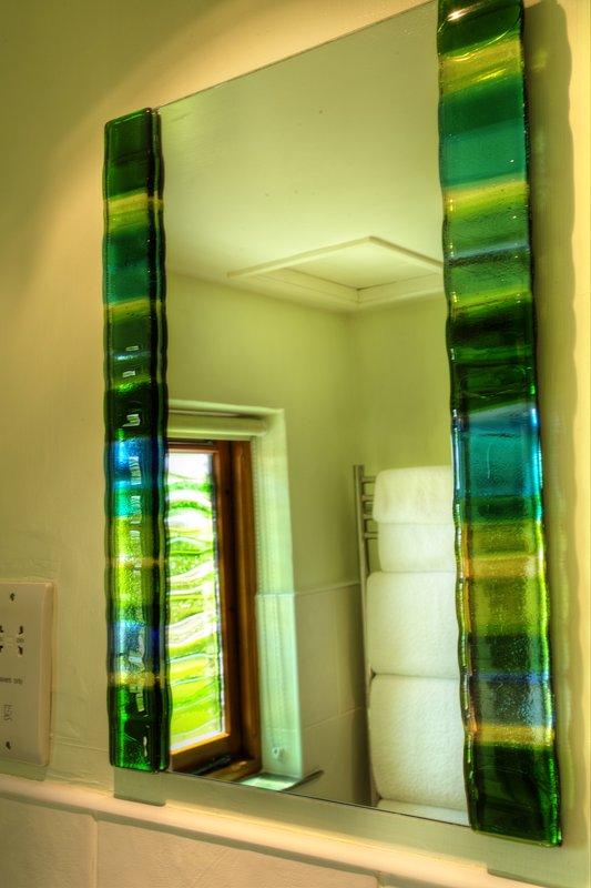 Jo Downs maakte de gesmolten glas ramen in zowel de badkamers.