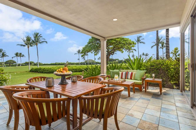 Generous Covered Lanai with Ample Seating and Views of the Hualalai Golf Course Green, Palm Trees, and Pacific Ocean Beyond.