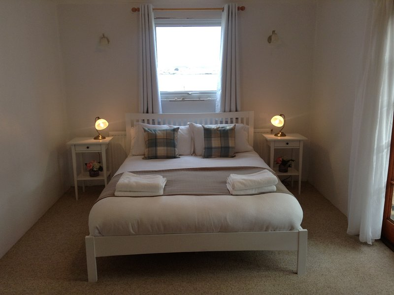 Our double room with kingsize bed and French doors leading to the conservatory.