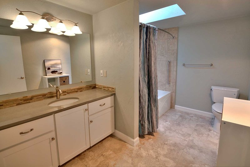 A clean and bright bath with  tile floors and tub/shower