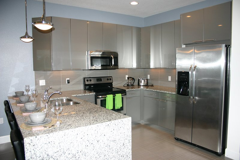 Modern kitchen with flat top stove, ice-maker fridge and all utensils.