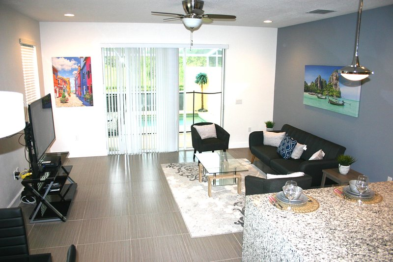 Spacious tiled living room leading out to splash pool for relaxing and fun times.