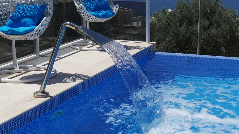 Infinity pool with jet fountain and hanging basket chairs