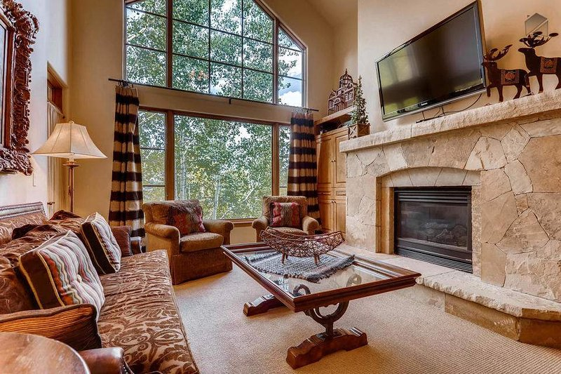 The living room has a huge gas fireplace and mounted flat screen TV.