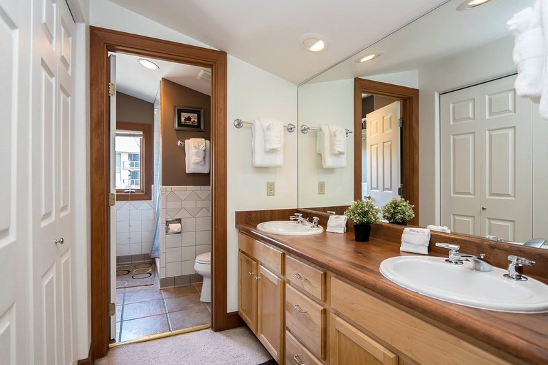 Sixth bathroom with dual sinks and walk-in shower on upper level
