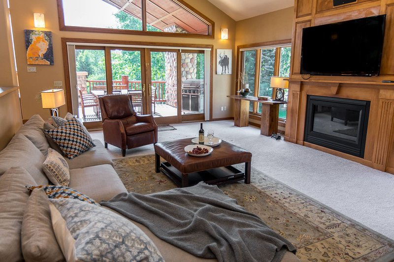 Main level lounge with flat screen TV, gas fireplace, and deck access