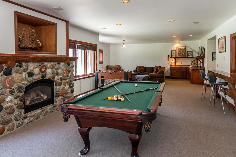 Enjoy a game of billiards or foosball next to the fireplace with easy access to refreshments stored at the wet bar