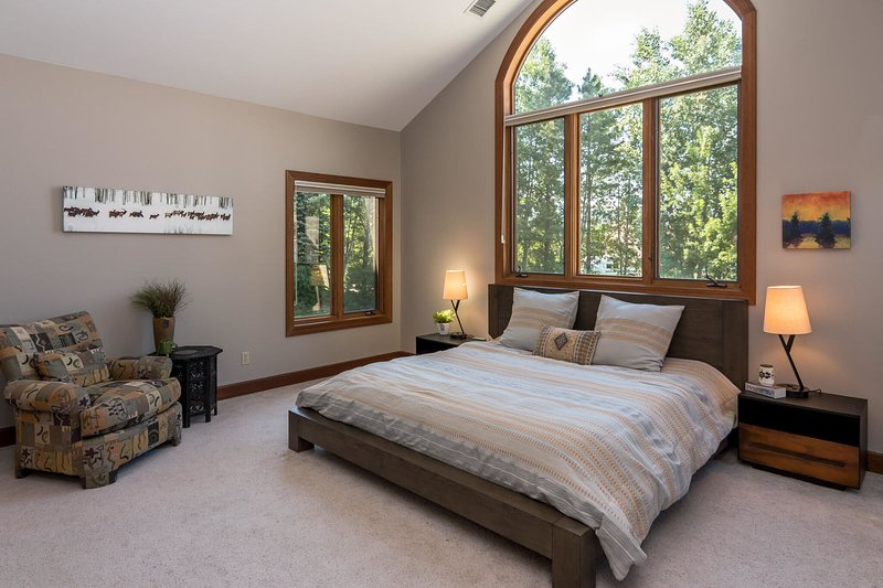 Third bedroom with King surrounded by forest views (main level)