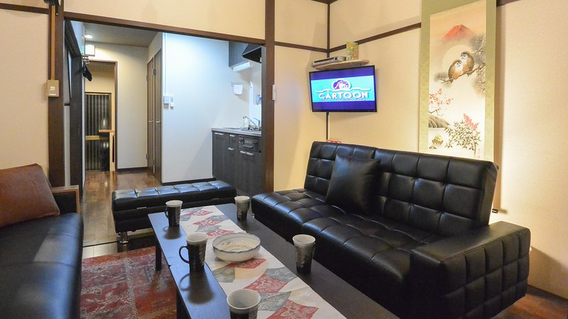 The living room with a wall mounted TV and DVD player.