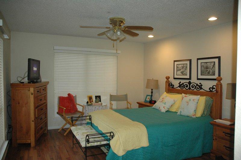 la planta baja dormitorio principal con cama de matrimonio y TV. Se abre hacia el patio trasero.