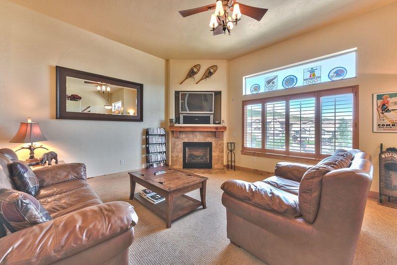 """Sala de estar del nivel principal con muebles cómodos, TV de 42 """"y chimenea a gas"""
