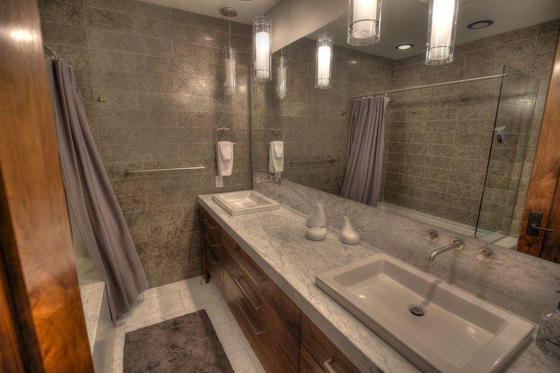 Ground Floor / Basement Level - Master Bathroom with shower tub/combo and double vanity sinks.