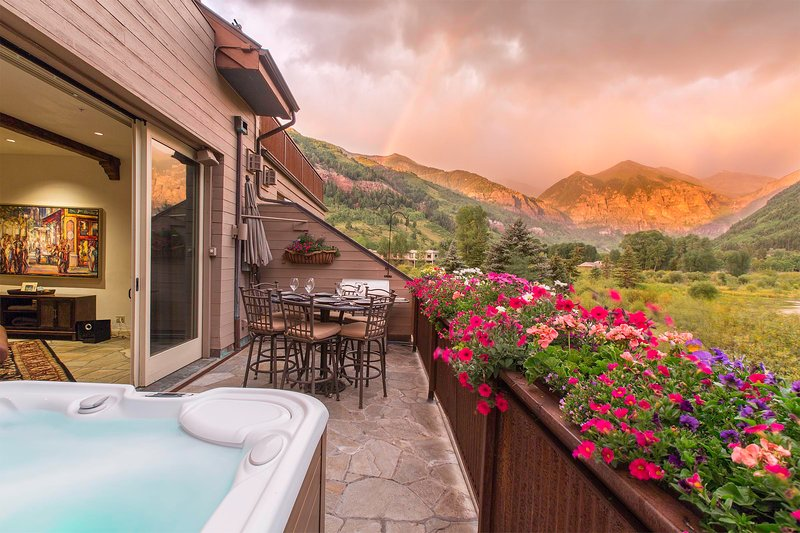 Outdoor dining area with hot tub and beautiful mountain views.