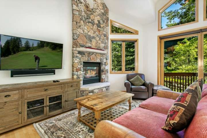 Bright living room with gas fireplace, large flat screen TV and floor to ceiling windows.