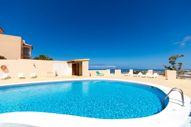 Communal pool, terrace and sea views in background.