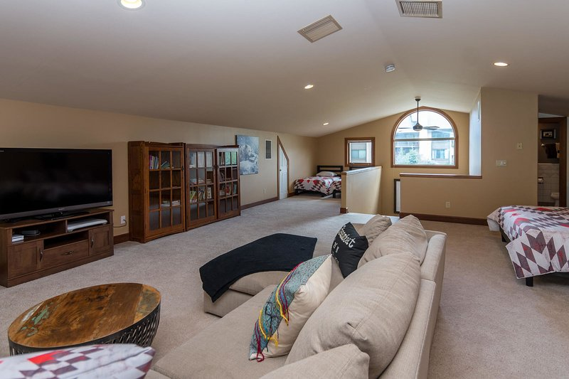 Sectional sofa in the loft surrounds a flat screen TV with Nintendo Wii game system
