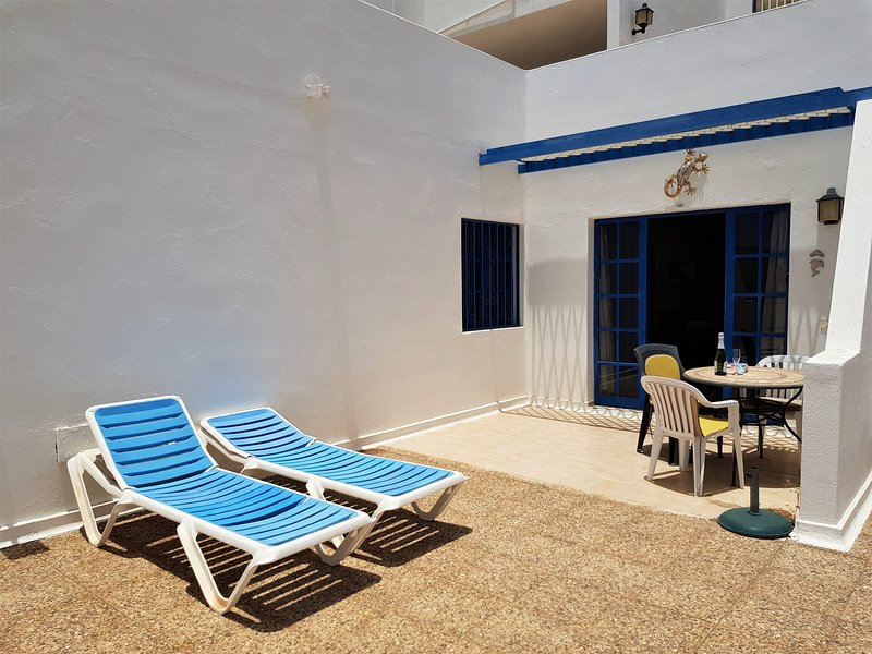 The apartment has open and sheltered outside space furnished with table, chairs and sunloungers