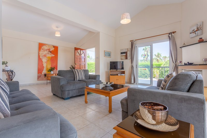 Open-plan living room with dining area, kitchen, deck access, WiFi Internet, Satellite TV, and DVD player