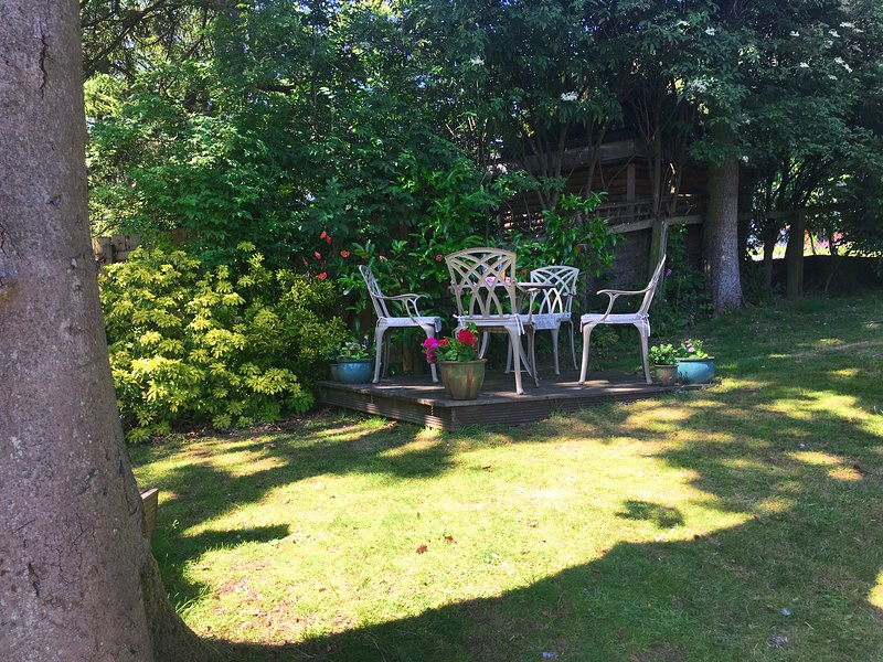 Cottage patio area in a peaceful woodland garden with wildlife.