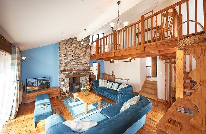 Alto salón espacioso con estufa de leña, escalera de caracol y mezzanine arriba