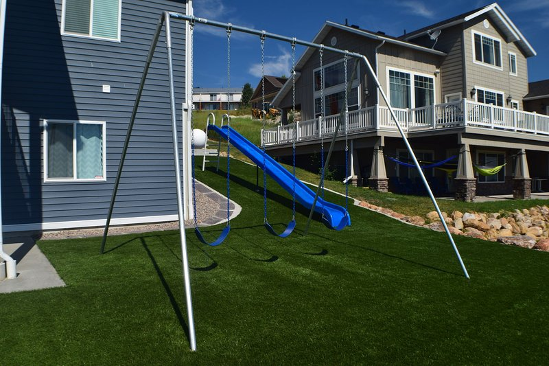 Outdoor swing set and slide looking over the lake