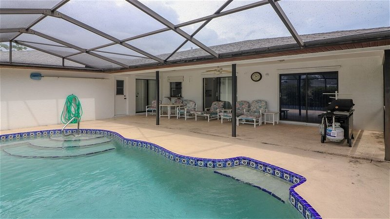 Covered lanai with view of guest bath, den and dining room and master sliding doors.