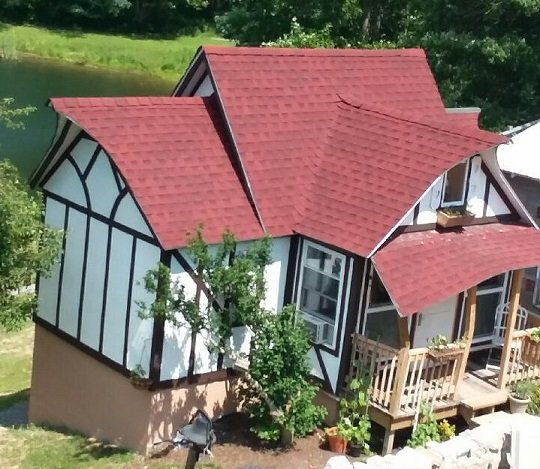 An aerial view of the Storybook Cottage- the pond is in the rear & there is a seating area in front.