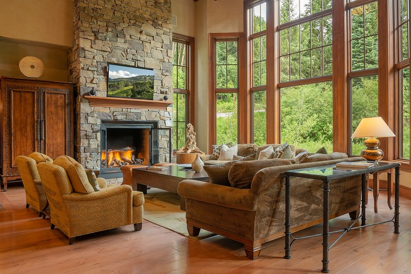 Great room with gas fireplace, ample seating, and floor-to-ceiling windows