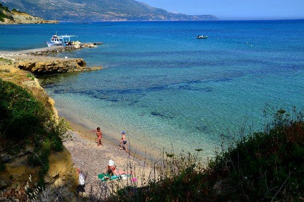 Praia de Spartia: águas rasas, costa arenosa, rochas acima e abaixo da água para o salto do penhasco e snork