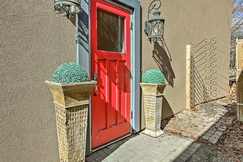 La puerta roja vibrante actúa como su puerta de entrada a la relajación privada en la ciudad.