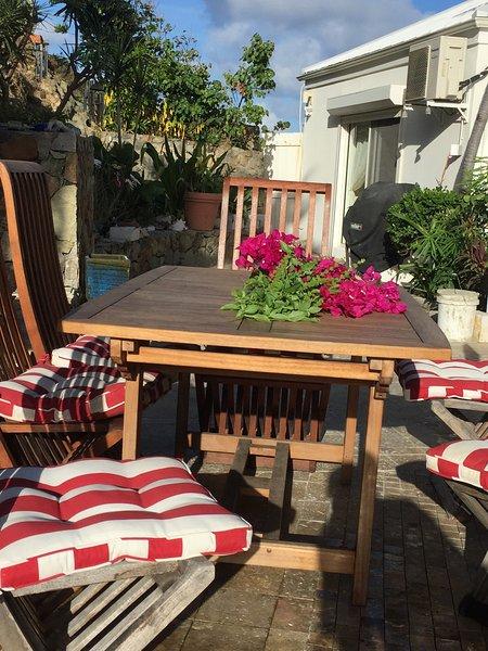 Table et chaises à côté de la zone barbecue-Grill et fumeur. Ceci est à l'avant de la Villa 2018.