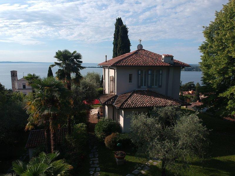 Vista frontal de la villa con iglesia y lago