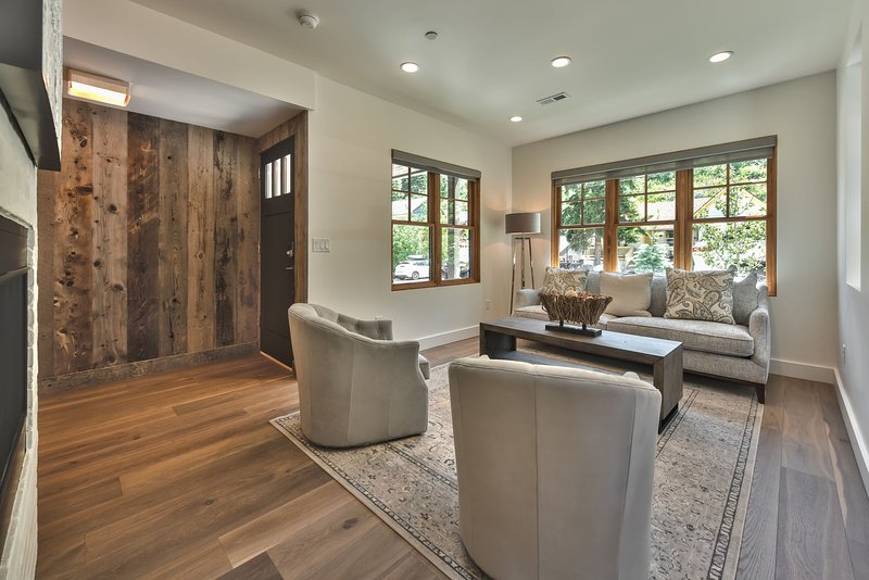Entrada frontal a la gran sala con decoración profesional: sala de estar, área de comedor y cocina con hermosos pisos de madera noble en todo el edificio