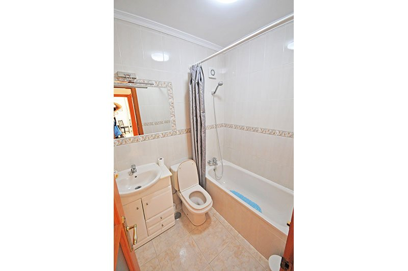 Salle de bain carrelée avec baignoire