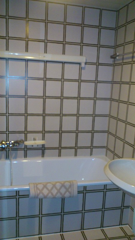 bathroom with bathtub, clothes rack and hairdryer